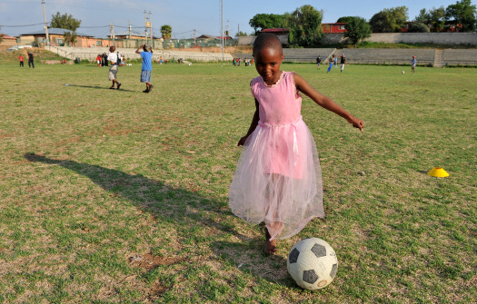 Girl in pink paying soccer